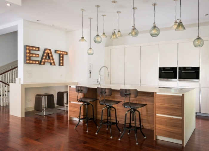 cocinas americanas, cocina moderna con barra en blanco, decoración en la pared y muchas lámparas colgantes de diferente forma