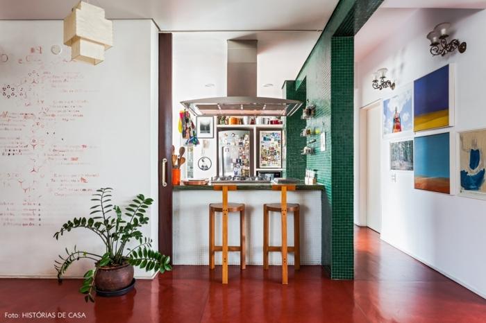 barra americana, cocina en blanco, rojo y verde, paredes en blanco con pinturas marinas, barra con dos sillas de madera de dos piernads