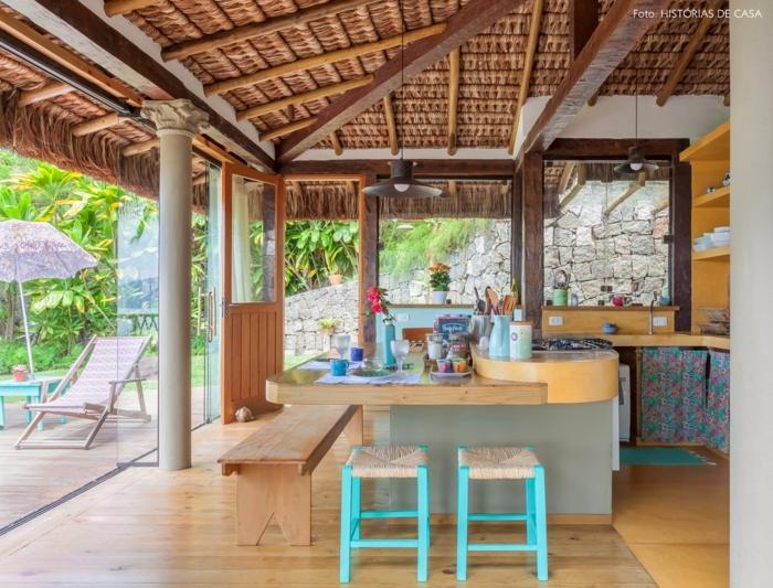 barra americana, cocina de verano, barra oval de madera, pequeñas sillas en azul, banco de madera y suelo de parquet