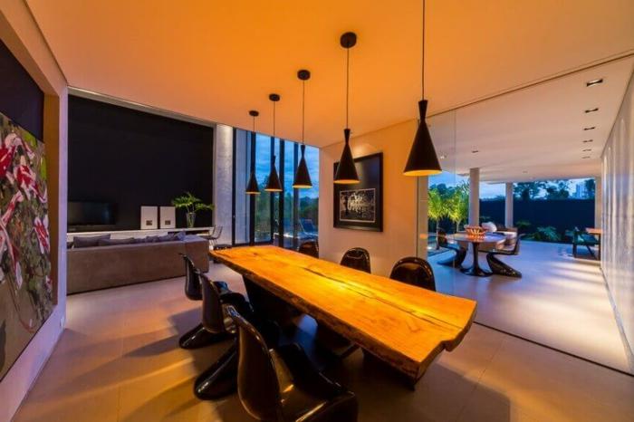 salon comedor, iluminación original para un comedor moderno con mesa alargada de madera y sillas negras modernas, paredes con decoración