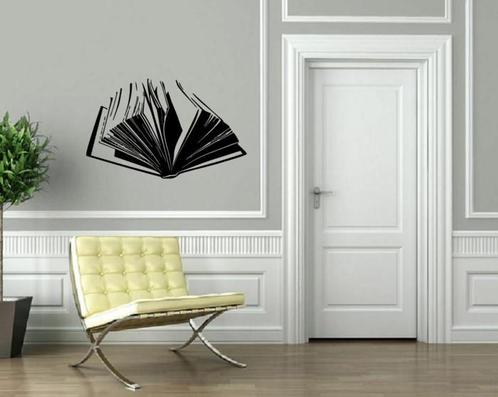 vinilos pared, salón con paredes en blanco y gris, vinilo negro de libro abierto con efecto 3D, sillón amarillo