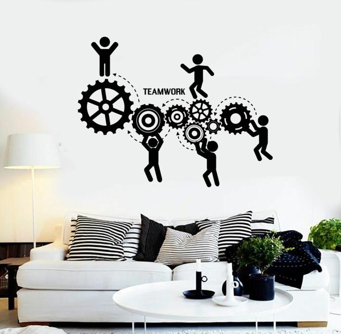 vinilos pared, salón con sofá y cojines en blanco y negro, vinilo negro con ruedas y figuras humanas, trabajo en equipo