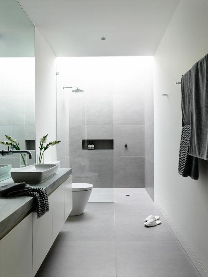 cuartos de baño con ducha, baño llargo y estrecho en color gris, ducha de obra con nicho en la pared, mampara de vidrio