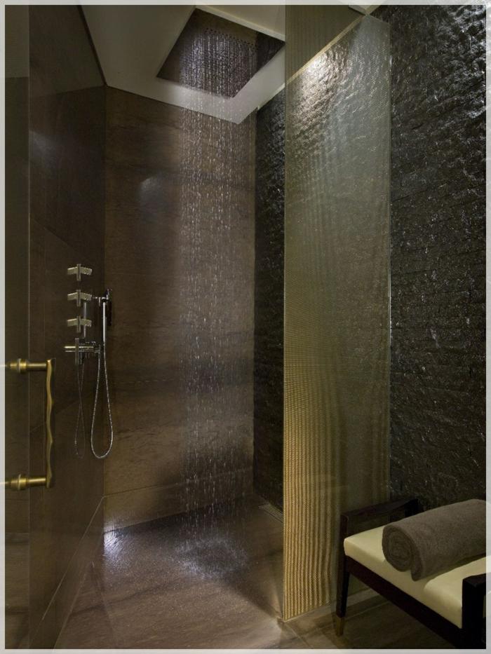 cuartos de baño con ducha, ducha de obra moderna con efecto de lluvia, puerta de vidrio con asa dorada, banco tapizado y toalla
