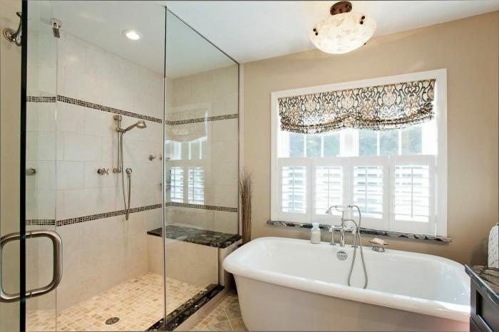 cuartos de baño con ducha, baño con bañera y ventana grande, ducha de obra con suelo de baldosas, banco de granito y mampara de vidrio