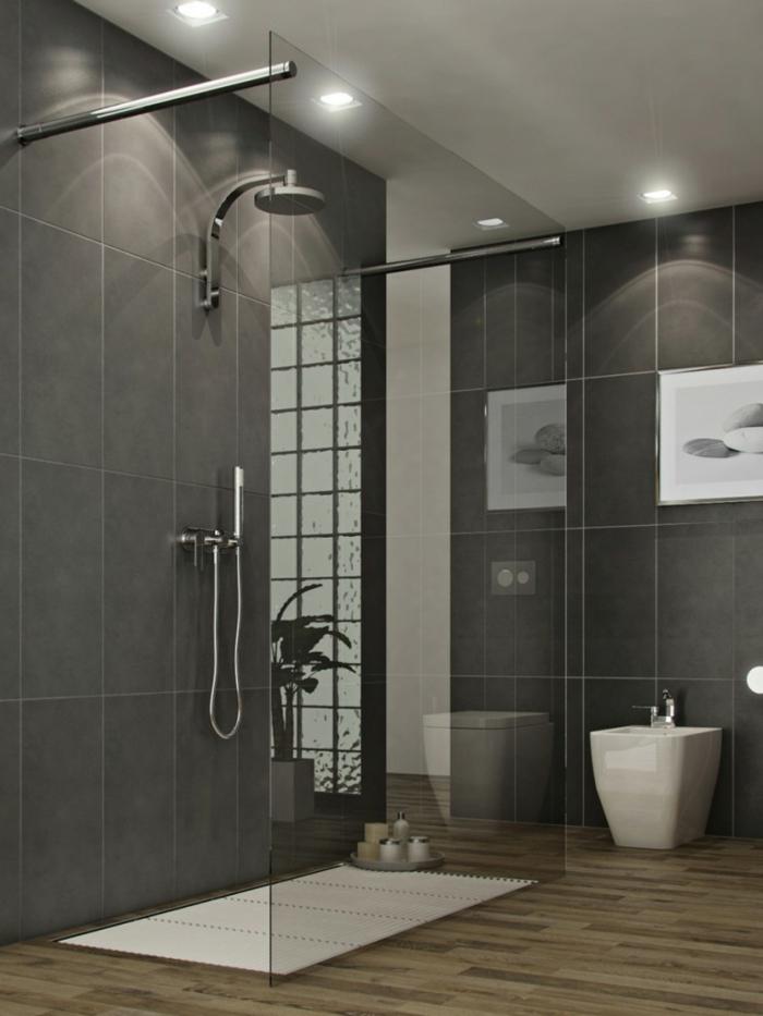 cuartos de baño con ducha, baño con suelo de madera y paredes con baldosas gris, cuadro con piedras, ducha de obra con rejilla blanca y mampara de vidrio