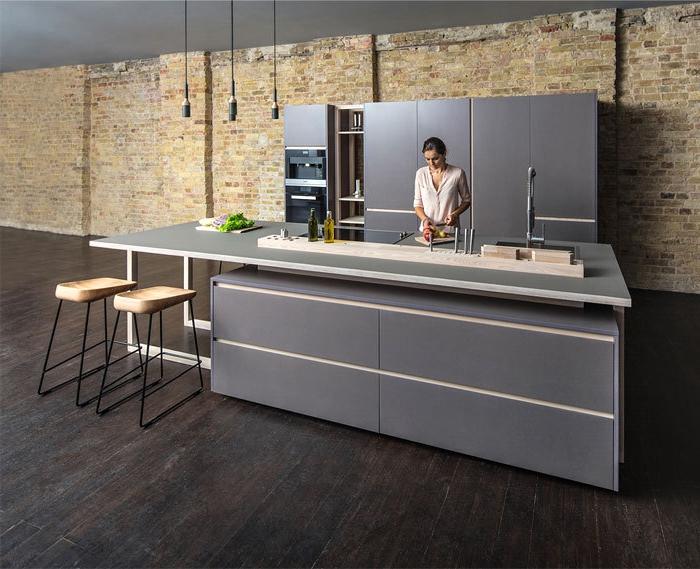 salon cocina, cocina moderna en estilo minimalista, barra y armarios en gris, suelo de madera y paredes con ladrillos, lámparas colgantes