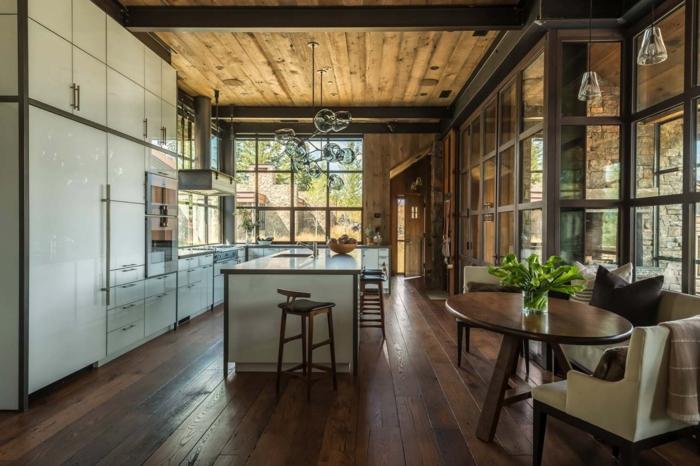 salon cocina, cocina espaciosa en un salón con entorno de madera, armarios grandes blancos, lámparas originales, comedor pequeño