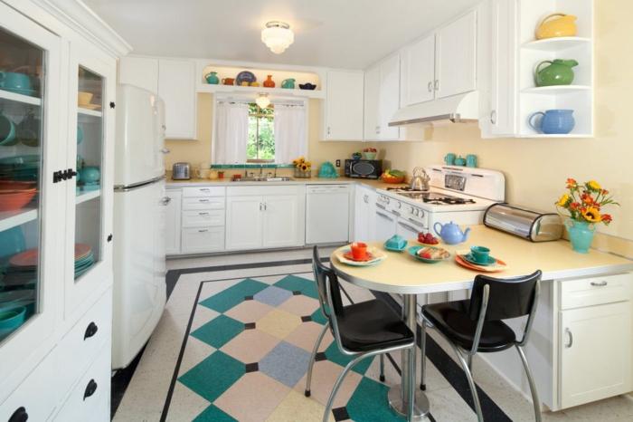 salon cocina, cocina con muebles blancos y detalles en azul y verde, barra oval en l con dos sillas negras