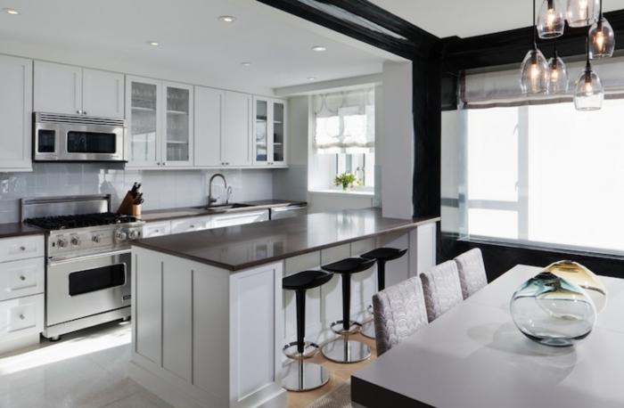 salon cocina, cocina clásica en blanco y negro con barra americana y sillas modernas, lámpara original que imita copas de vino colgantes