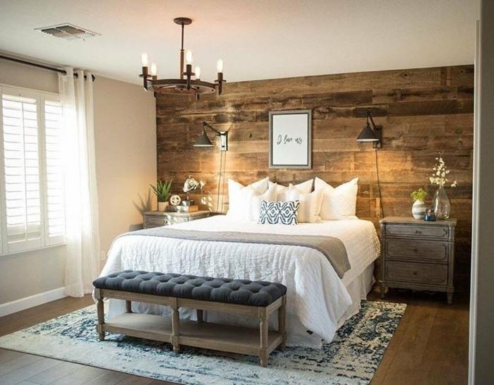 cabecero de madera, habitación en estilo rústico, pared destacada con vigas de madera, pie de cama de madera y peluche en gris