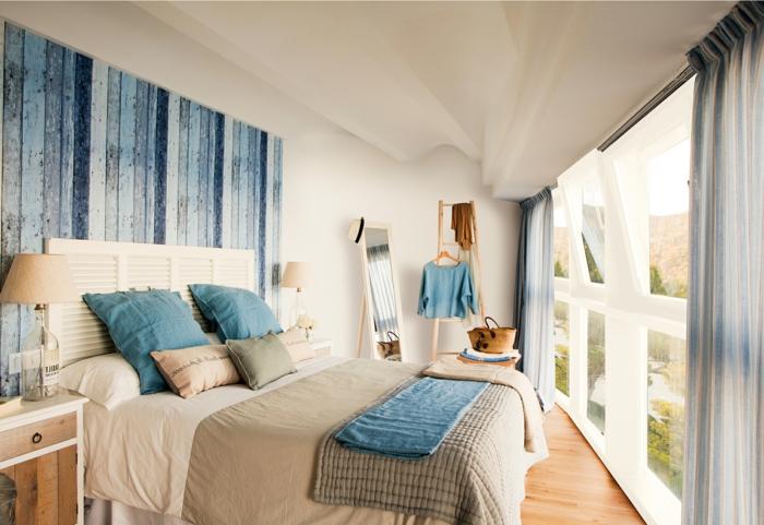 cabecero cama, precioso ejemplo de dormitorio con vista en estilo marinero, grandes ventanales y cabecero que imita madera en azul