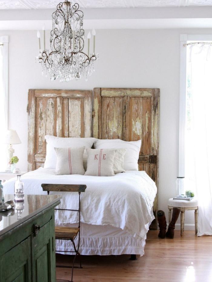 cabeceros, puerta vieja reutilizada para hacer cabezal vintage, candelabro masivo blanco, cama de medio tamaño con sábanas en blanco, toque rústico
