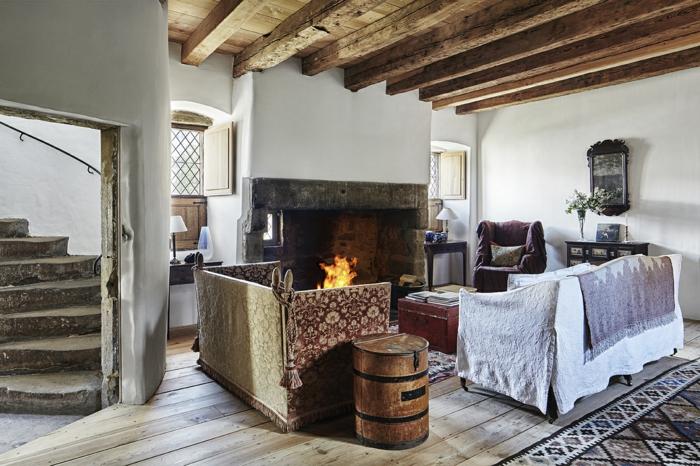 chimeneas rusticasa, espacio en estilo rústico con techo de vigas de madera, sofás vintage y chimenea grande