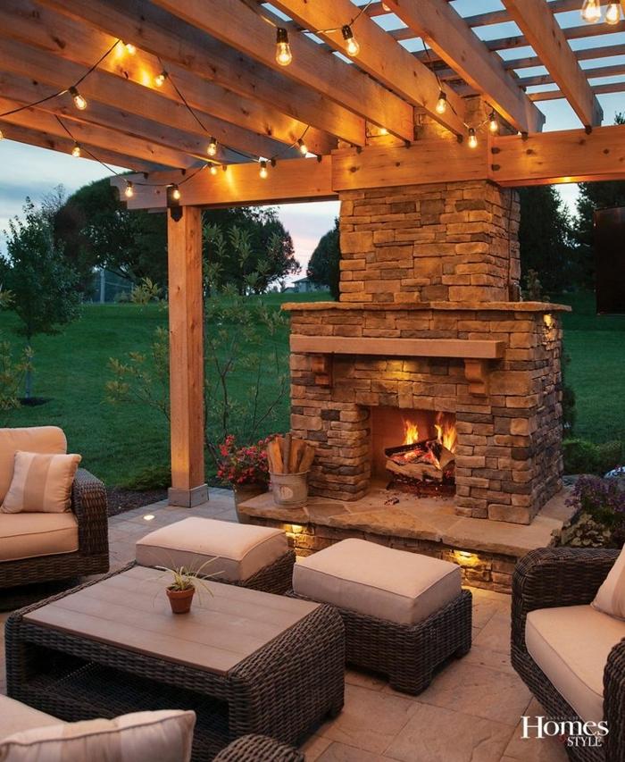chimeneas rusticas, grande chimenea de piedra en la veranda, techo con vigas de madera, muebles de mimbre