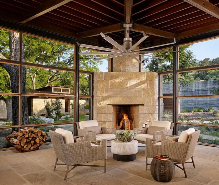 chimeneas rusticas, interior con grandes ventanales, muebles de mimbre y grande chimenea de madera