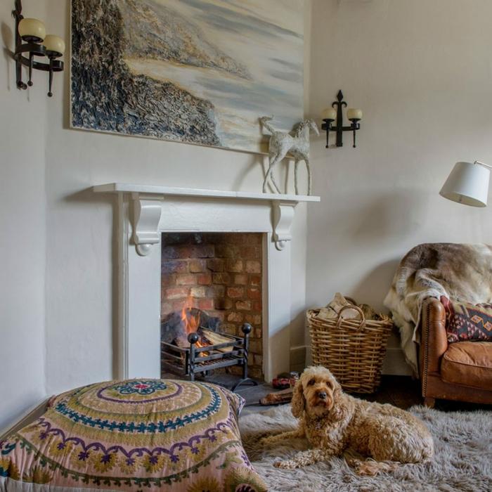 estufa leña, interior bonito en blanco con chimenea acogedora, alfombra peluda y lámparas vintage