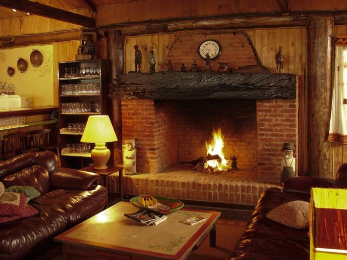 estufa leña, interior en estilo rústico, grande chimenea de ladrillos con viga de madera, sofás de piel en marrón