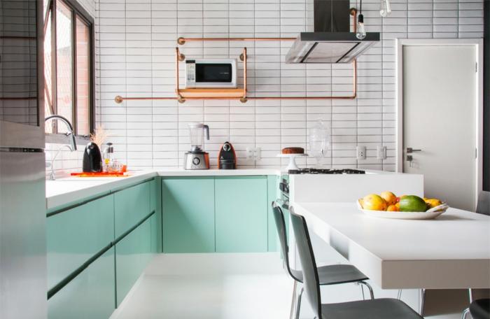 salon cocina en tonos claros, armarios en color verde menta, paredes con azulejos en blanco, mesa blanca, detalles en bronce