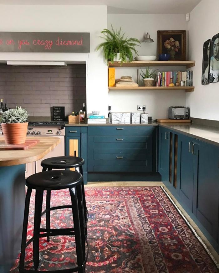 cocina tradicional, cocina con barra de madera, armarios pintados en azul, dos sillas de barra negras, estantes de madera