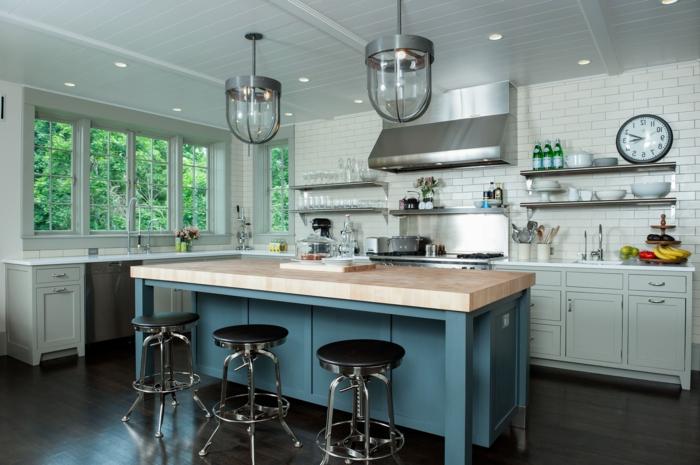 salon cocina, cocina americana con barra en azul y sillas en negro, lámparas y campana extractora en estilo industrial, paredes con azulejos que imitan ladrillos