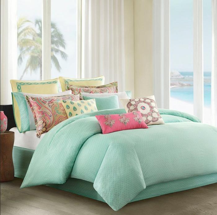 tonos de azul, dormitorio pequeño en colores claros con vista al mar, cobijas en verde azul y cojines decorativos en colores pastel