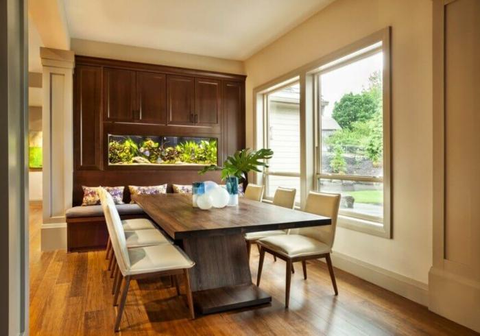 mesas de comedor moderno, larga mesa de madera con sillas en beige y armario de madera con banco empotrado, vista al jardin