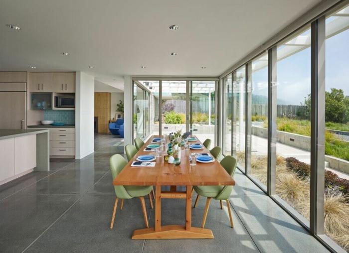 muebles de salon, comedor grande con mesa de madera y sillas verdes, grandes ventanales altos y lámparas empotradas en el techo