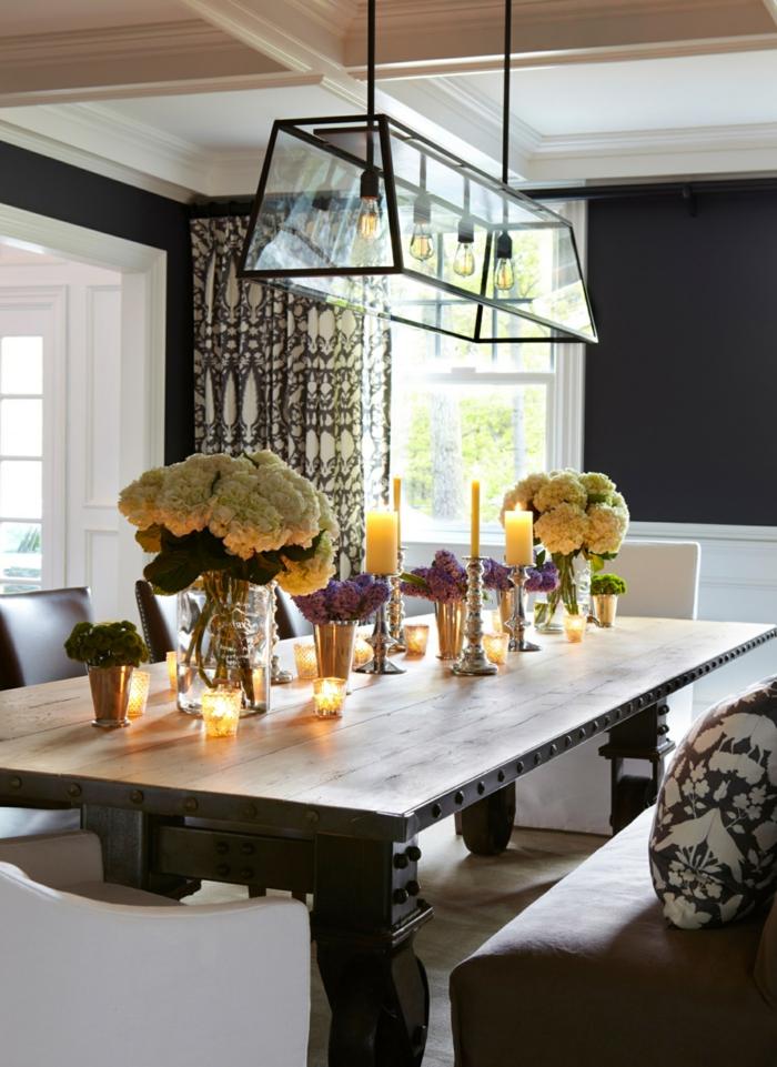 muebles de comedor, comedor con toque rústico, grande mesa de madera y mucha decoración de flores y velas, paredes en negro