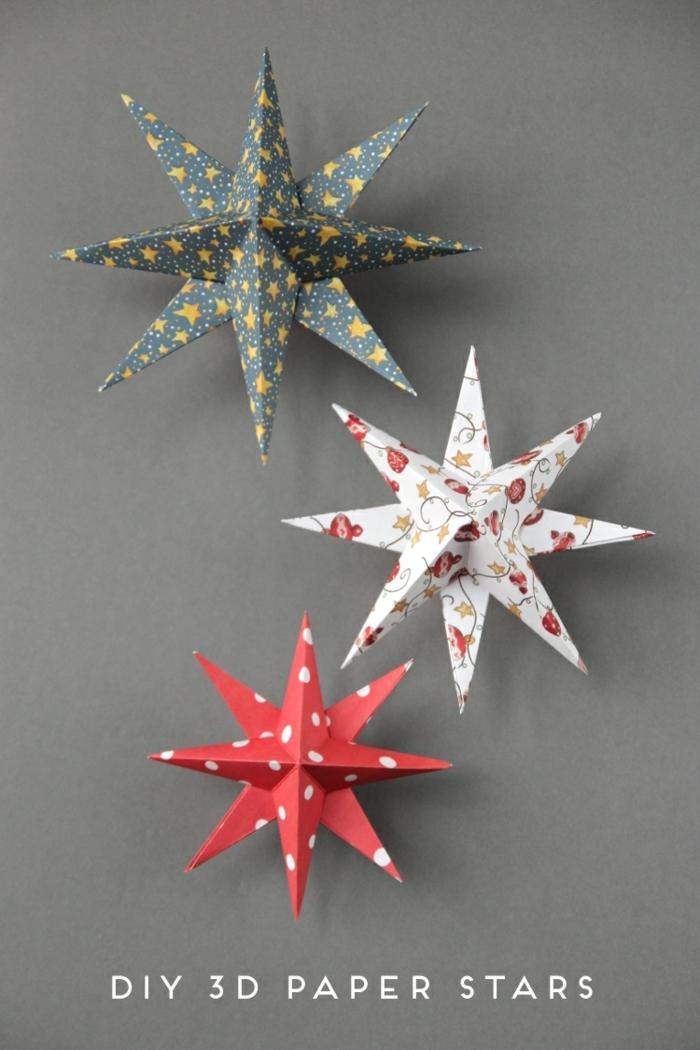 estrellas de papel, tres adornos navideños caseros hechos de cartón en forma de estrellas de ocho puntos