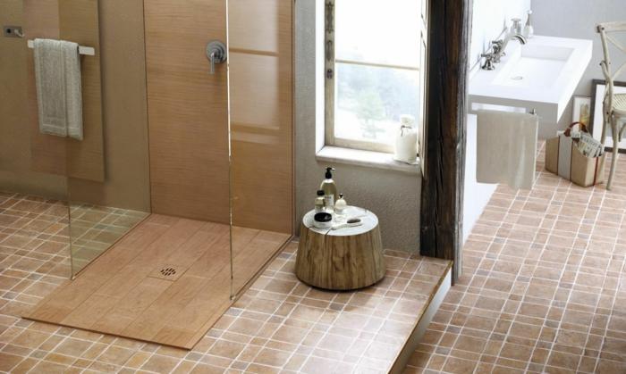baños pequeños con ducha, baño con mucha luz, ducha de obra con plato de madera, suelo de baldosas, ventana y lavabo blanco