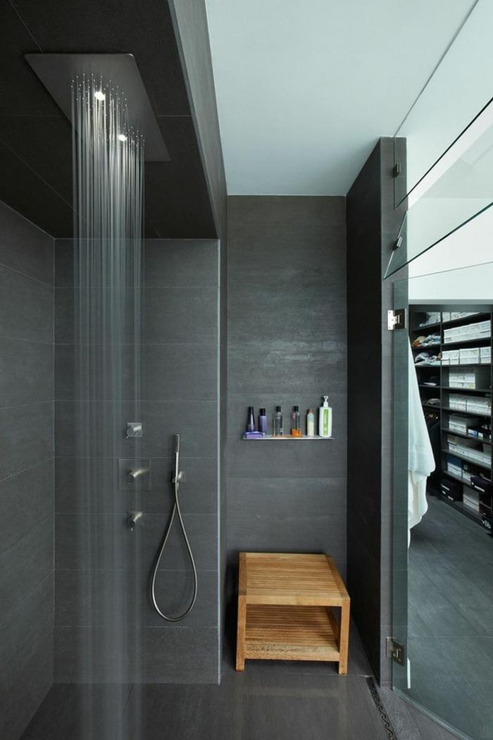 baños pequeños con ducha, baño moderno negro con banco de amdera. ducha de obra con efecto de lluvia y ducha de mano, suelo laminado