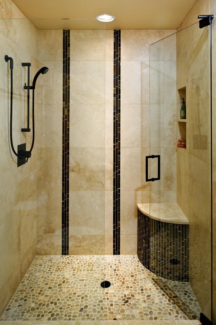 baños pequeños con ducha, baño con baldosas, ducha de obra con banco, ducha de mano negra, puerta de vidrio, suelo con piedritas