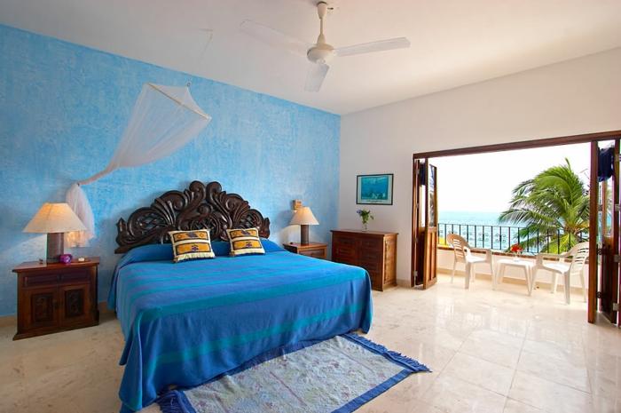 tonos de azul, bonita habitación con vista al mar y grande terraza, decoración marina, pared en azul con efecto vintage, grande cama de madera con cabecero en ornamentos