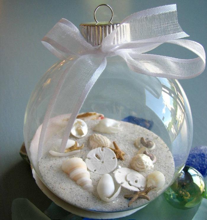 adornos navideños, manualidades originales para Navidad, bola transparente llena de elementos marinos con cinta blanca