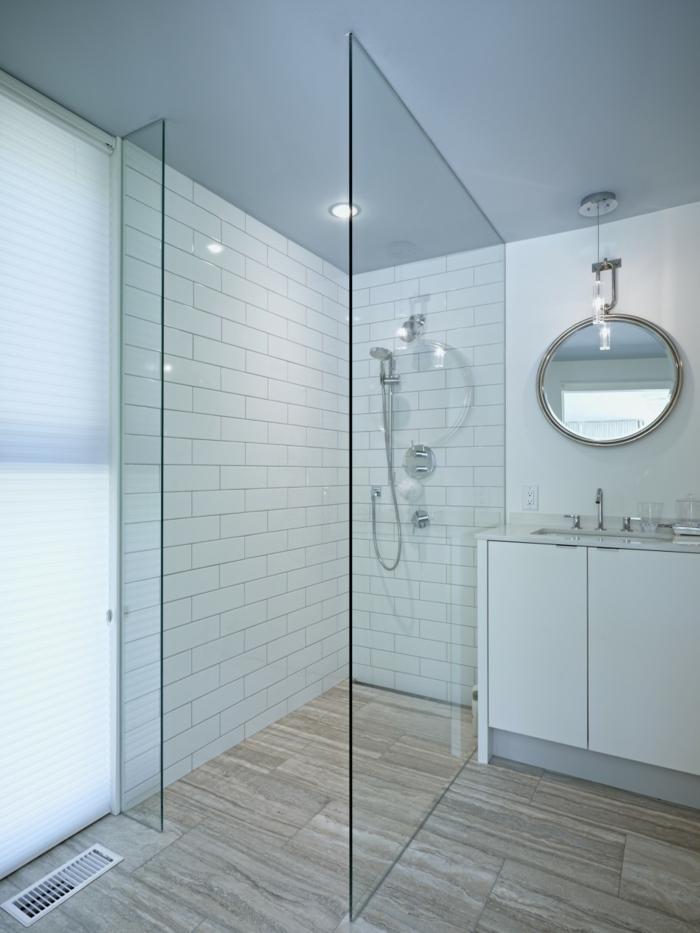 platos de ducha de obra, baño blanco, paredes con baldosas, espejo redondo, mampara de vidrio, suelo laminado