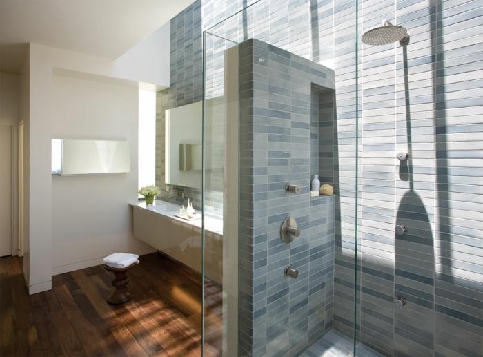 platos de ducha de obra, baño con paredes de baldosas azules, mucha luz natural, ducha de obra con efecto lluvia y nicho en la pared, suelo laminado