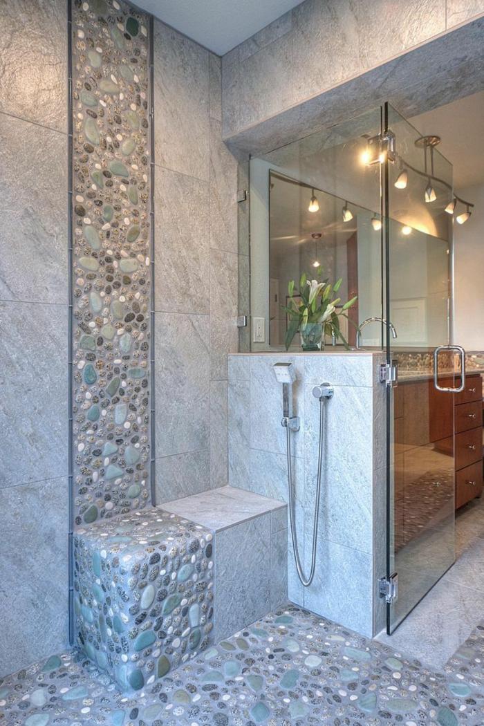 platos de ducha de obra, baño con paredes de granito, ducha de obra con suelo con piedras y banco, ducha de mano, puerta de vidrio