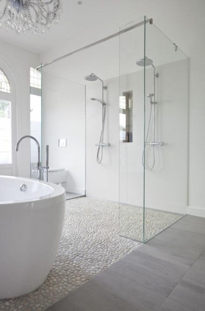 duchas modernas, baño grande con ventanales, suelo con baldosas y piedrirtas, bañera. ducha doble con mampara de vidrio, lámpara de araña