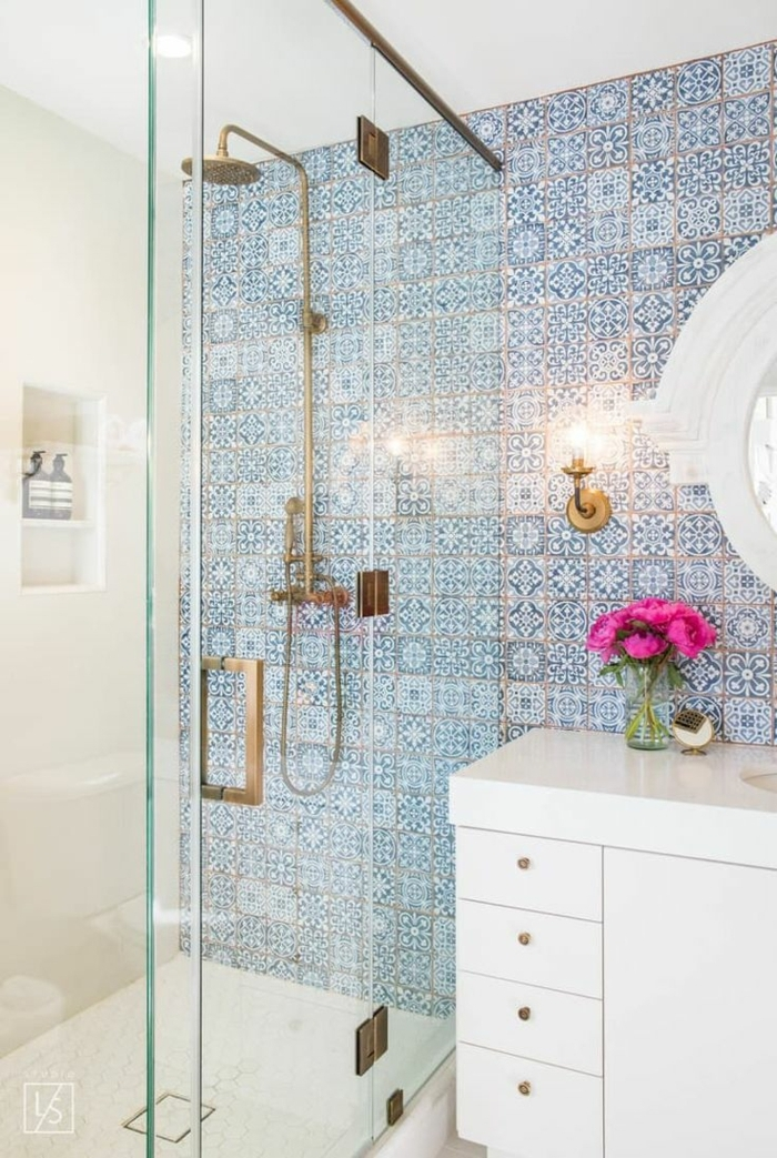 duchas modernas, baño pequeño con azulejos en tonos azules, ducha de obra con puerta de vidrio, palto de ducha, mueble blanco
