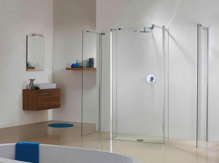 duchas modernas, baño minimalista con bañera y ducha de obra, mampara de vidrio, suelo laminado, lavabo y espjo pequeños