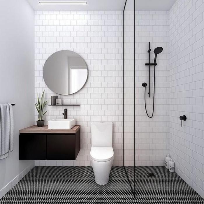 duchas modernas, baño pequeño en blanco y negro, lavabo pequeño, ducha negra de mano, mampara de vidrio, paredes con baldosas