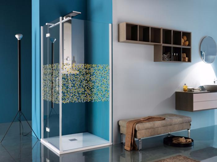 duchas de obra, cabina de cucha transparente con decoración en amarillo y azul, paredes en azul y blanco, banco tapizado