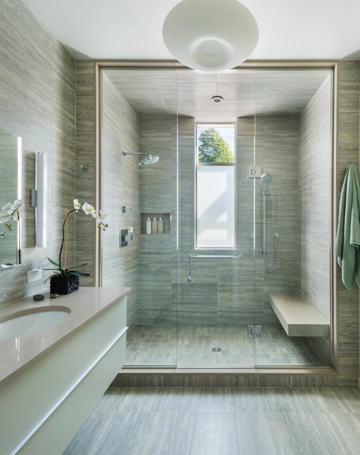 duchas de obra, baño con paredes y suelo laminado, ducha de obra doble con banco, maceta con orchidea, ventana larga y estrecha