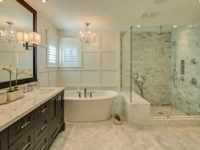 duchas de obra, baño grande, encimera de mármol, espejo ancho, bañera, ducha de obra con mampara de vidrio, lámpara de araña
