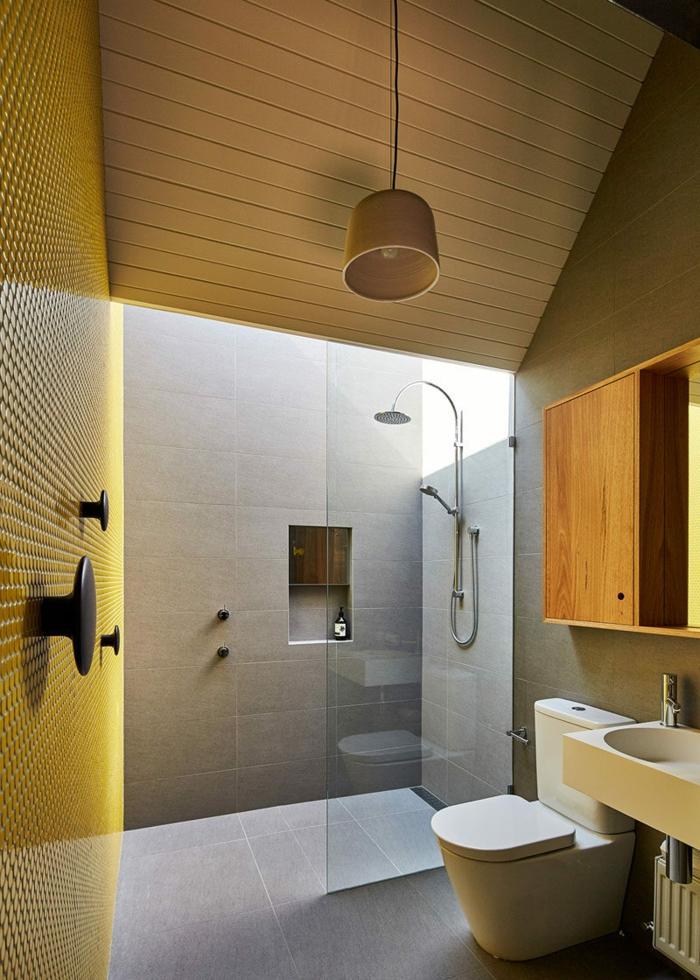duchas de obra, baño con techo inclinado con lamas de madera, pared amarilla, ducha con nichos en la pared, suelo con baldosas
