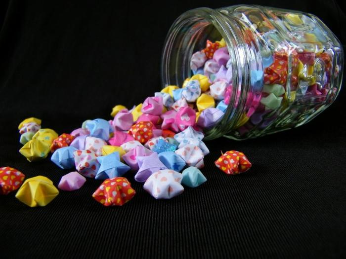 como hacer estrellas de papel, pequeños adornos en forma de estrellas, frasco lleno de motivos navideños en diferentes colores