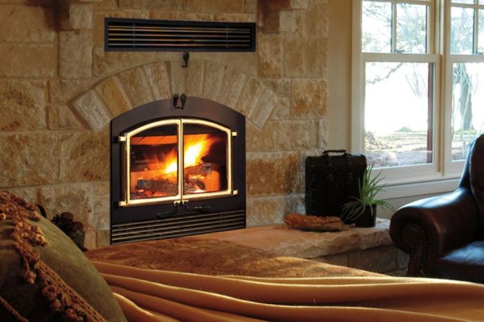 estufa leña, interior en estilo rústico, estufa moderna con puerta, construcción de piedra, cama con cobija de peluche color ocre
