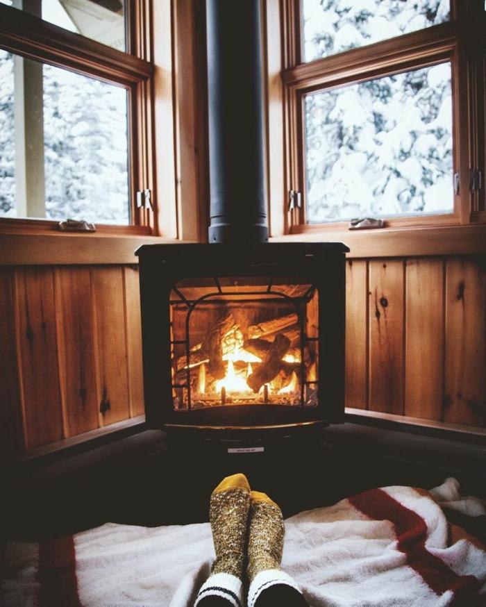 estufa leña, cama acogedor al lado de la estufa de leña, casa rural con paredes con vigas de madera, ventanas con vista invernal