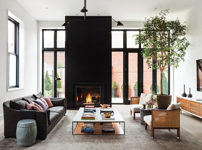 chimeneas modernas, grande chimenea alta en negro, salón moderno con mesa baja, grandes ventanales y planta alta decorativa